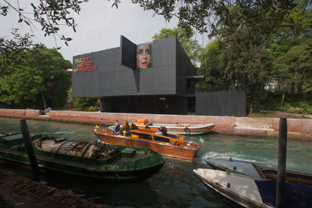 This photo provides a view of a rectangular, grey clad building from across a small river, framed by tree branches. Five small boats drift along the waterway, only one of which has people on board.  'Tracey Moffatt My Horizon' is written on the left side of the front facing facade. On one panel of the facade, which is marked by a grid, the face of a white woman with a startled gaze appears as if she is looking out of the building's window. She appears to be looking with concern towards the boats that are filling the river.