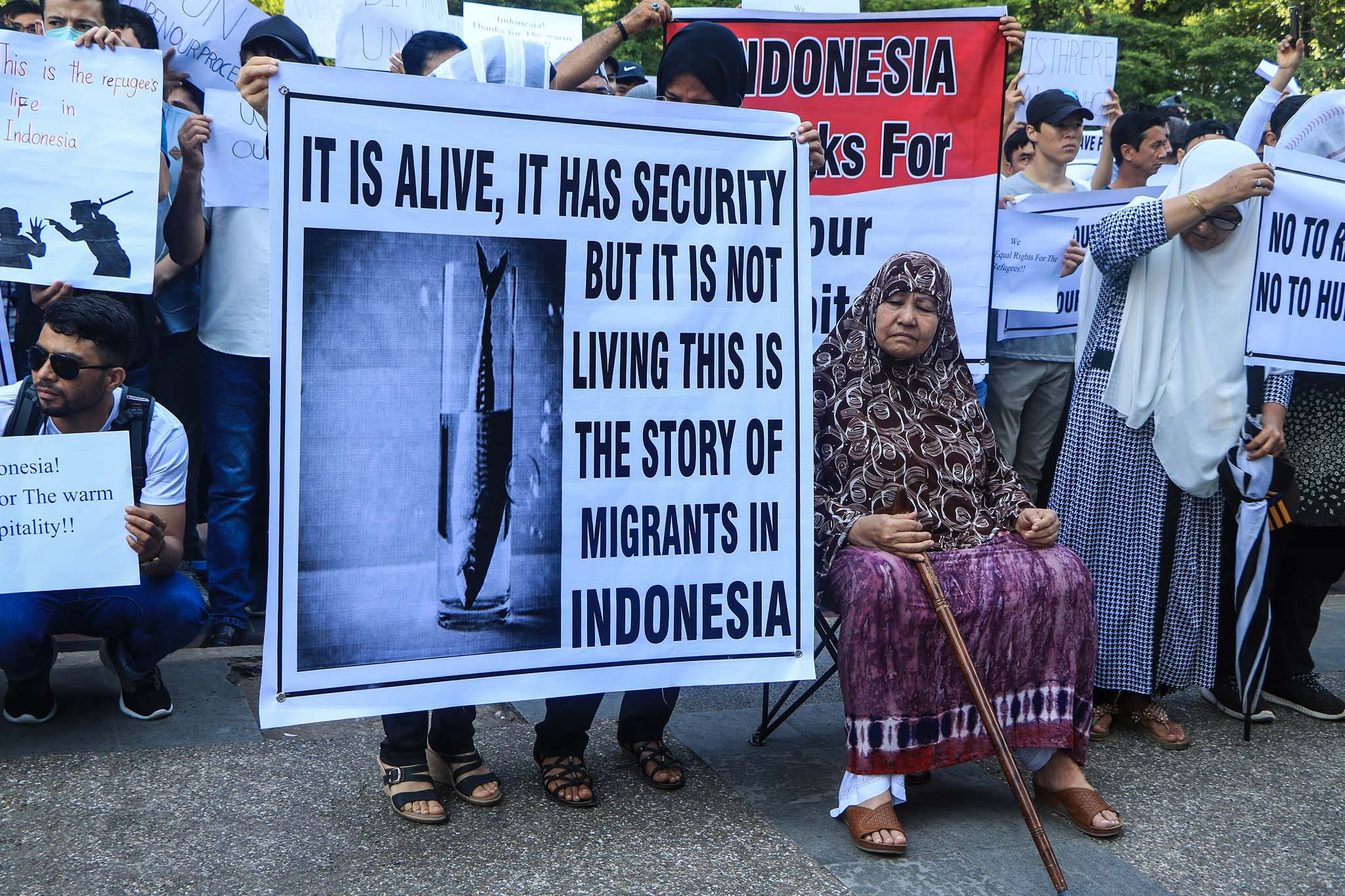 A group of people protest, many of whom are holding signs. A woman sits beside one of the placards, on a fold-out chair, holding a walking stick. The sign beside her depicts a fish in a glass of water with the text 'It is alive, it has security but it is not living this is the story of migrants in Indonesia'.