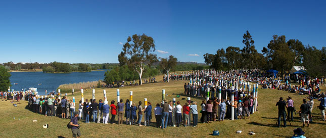A large group of people gather along the SIEV memorial which is comprised of a series of white poles of varying heights that snake around a parkland and edge of a lake.