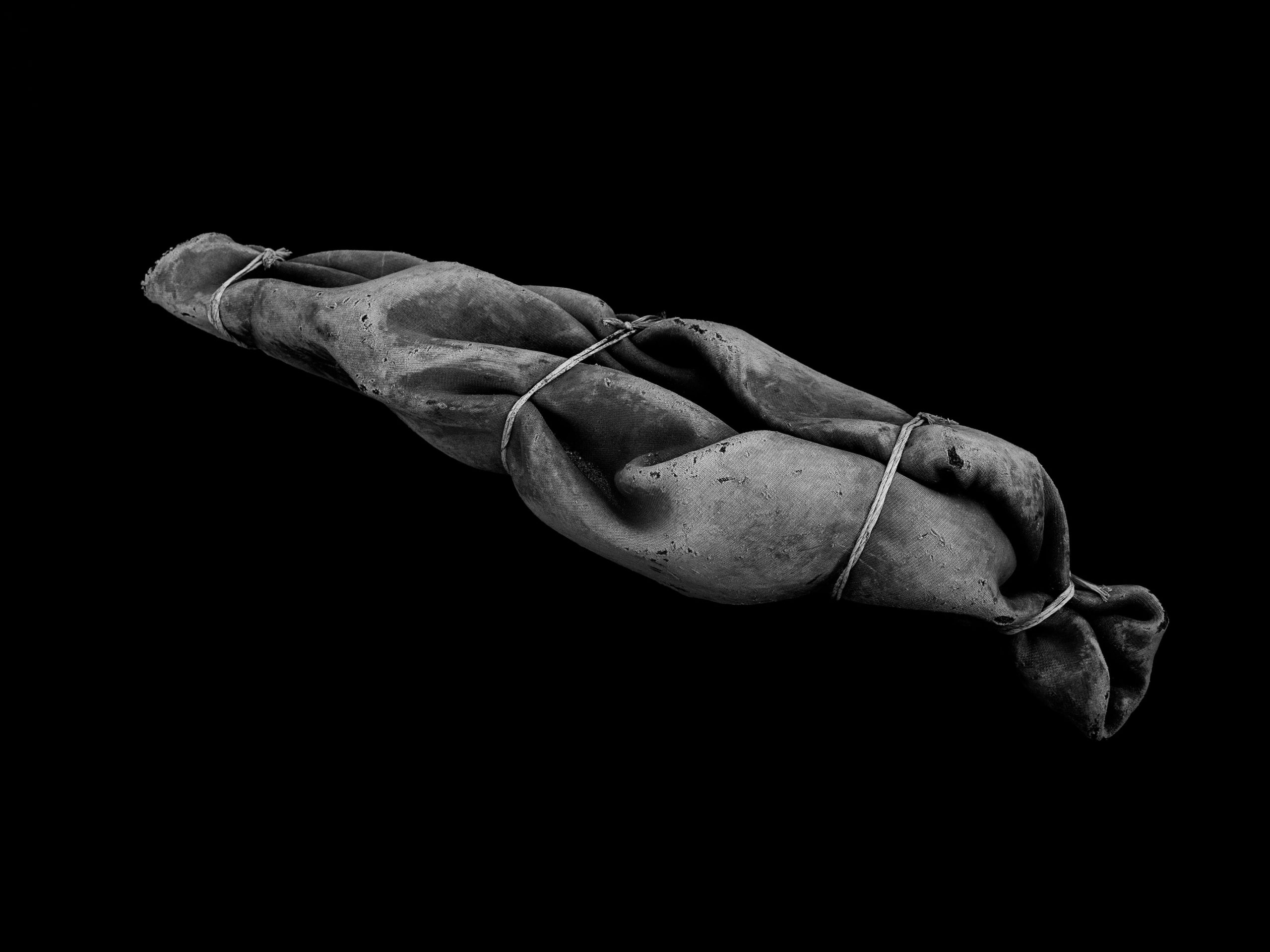Juxtaposed against a solid black background is a heavy grey blanket, tied in several places as if it is wrapped around a human body that has been dumped in the depths of the ocean.