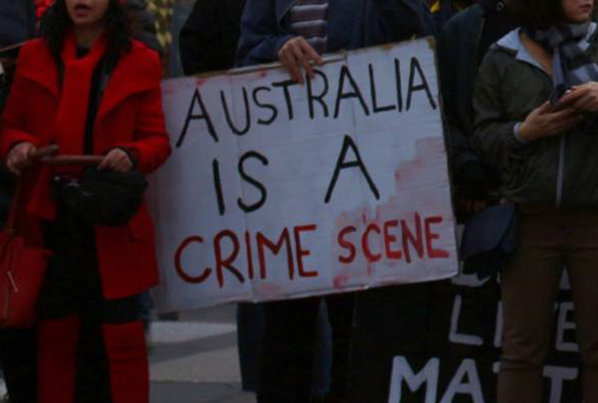 Placard being held by someone standing in a crowd of people at a protest, it reads 'Australia is a crime scene'. A woman standing to the left is wearing read and holding clap sticks.