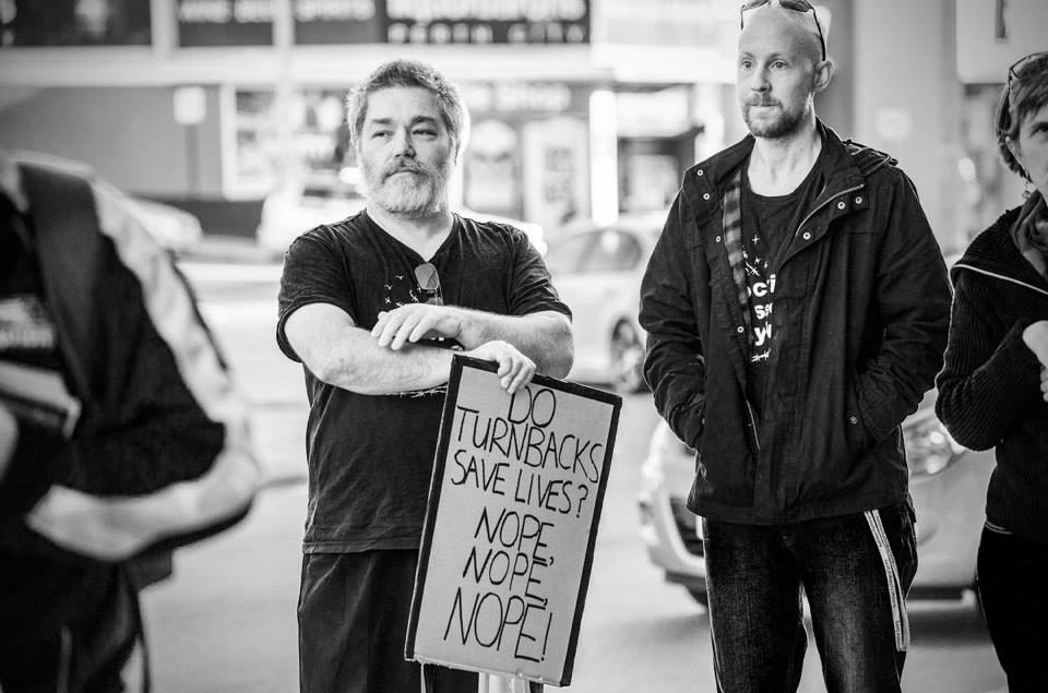 A man holds a placard at a protest that reads 'Do turnbacks save lives? Nope, Nope, Nope!'. A couple of people stand around him and cars can be seen driving past on the road behind them.