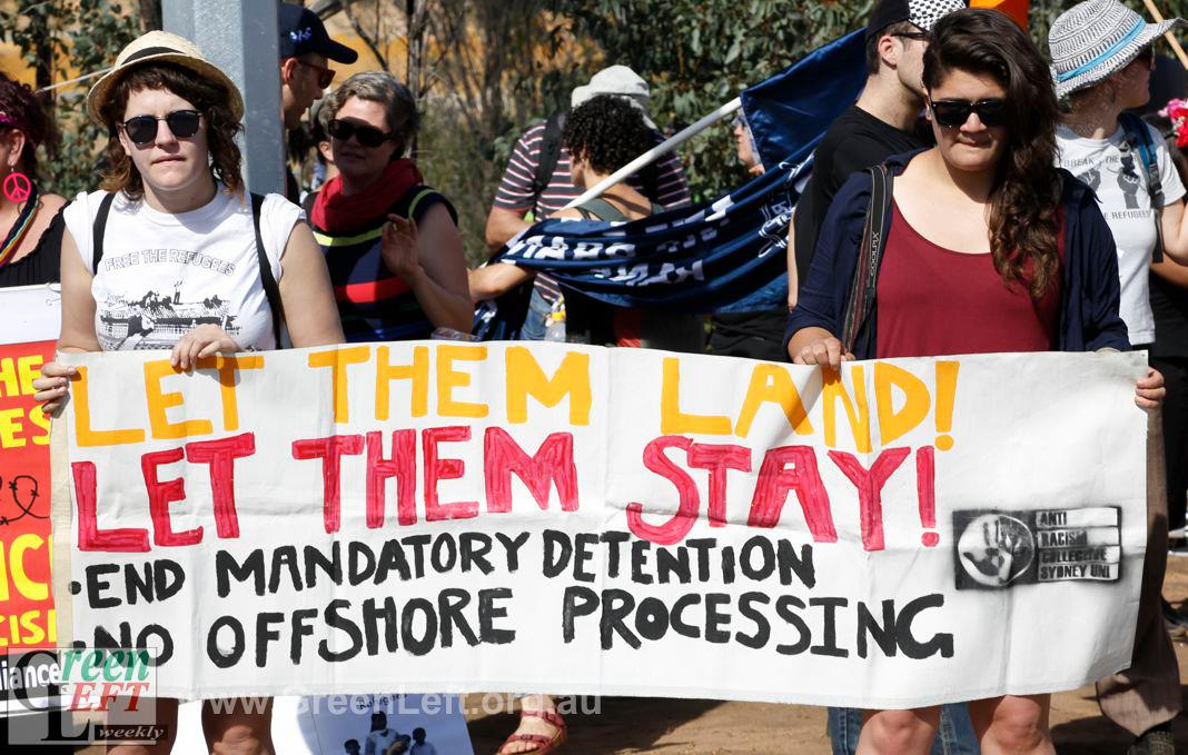 At a protest outside a detention centre, two people hold a banner that reads, 'Let Them Land! Let Them Stay! End Mandatory Detention. No Offshore Processing'.