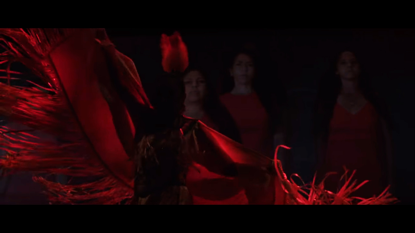 The silhouette of an Indigenous woman dancing while wearing traditional dress is in the foreground. Pictured on the screen behind her are three Indigenous women standing and looking at the viewer. They are all wearing red dresses.