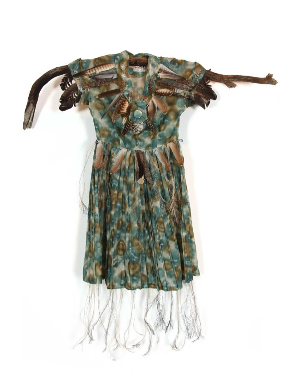 A vintage women's gown adorned with native Australian bird feathers is hung on a detached tree branch.