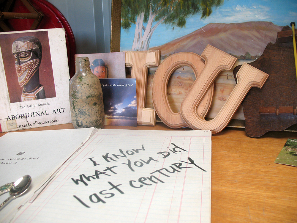 An open account book sits on a timber desk. Scrawled across the right page is the message, 'I know what you did last century'. Behind it a number of objects are propped up against the wall. These include an 'Aboriginal art book' by Charles P. Mountford, an old, dirty bottle, timber letters that spell 'I O U', a landscape painting and a piece of timber cut into the shape of Australia.