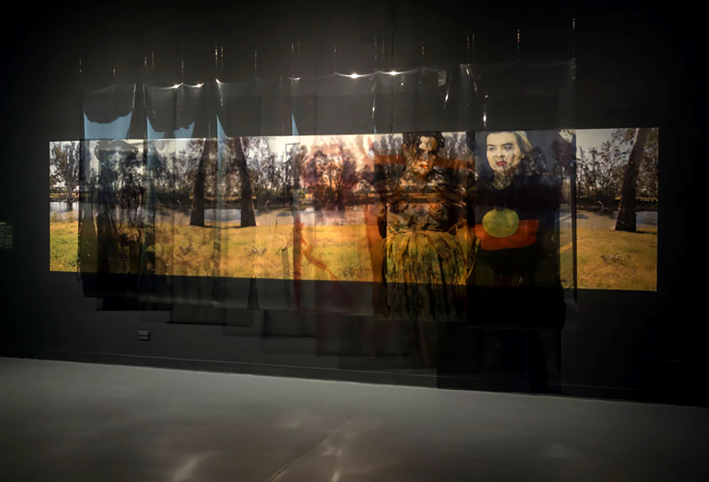 An installation that brings together layers of history through floating images of Paola Balla's ancestors positioned over matriarchal Country. Trees and a river can be seen in the photo background, along with a woman wearing the Aboriginal flag on her shirt.
