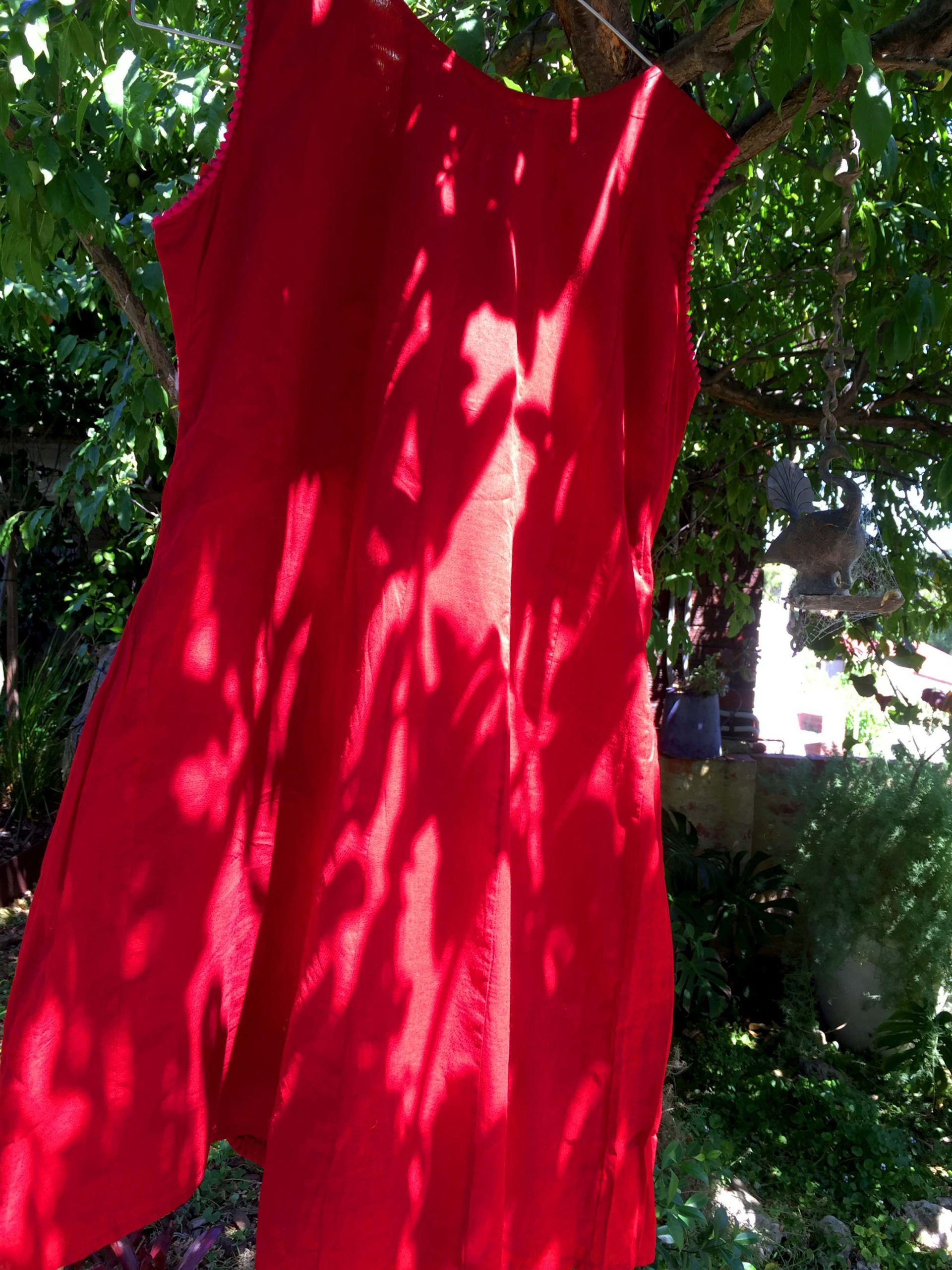 A red dress hangs from a tree, sunlight shines through the canopy projecting shadows onto the dress.