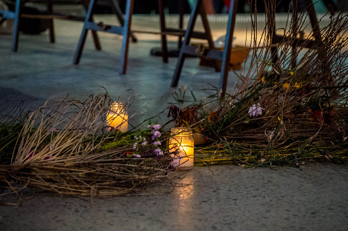 Native flowers and leaves are laid at a vigil on a concrete stage alongside candles in small glass jars.