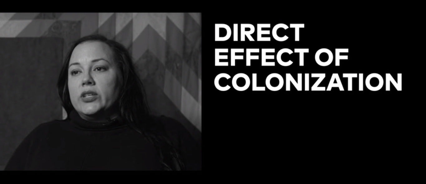 Screenshot from video. Woman on the left side and the words 'Direct effect of colonization' on the right.
