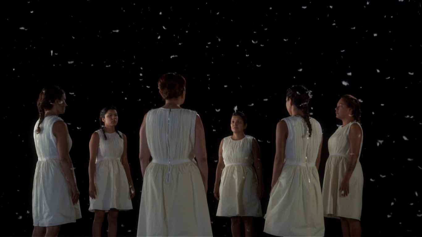A group of Indigenous women stand together in a circle, with their hands to their sides and looking towards the centre of the circle. They all wear white dresses and have their hair tied up. White feathers float down on them contrasting against the plain black background.