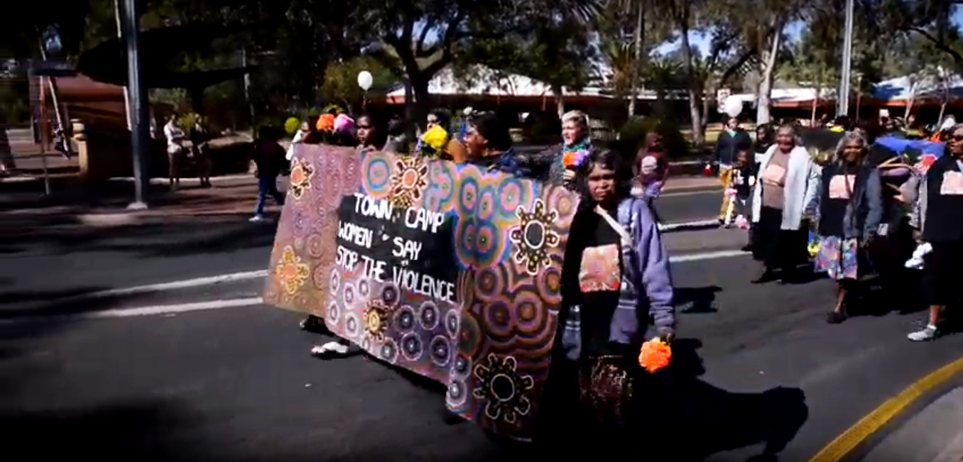 A group of women walk down the road in the centre of a small town. The women at the front carry a banner that reads 'Town Camp Women Say Stop the Violence'. Buildings and trees line the street in the background.