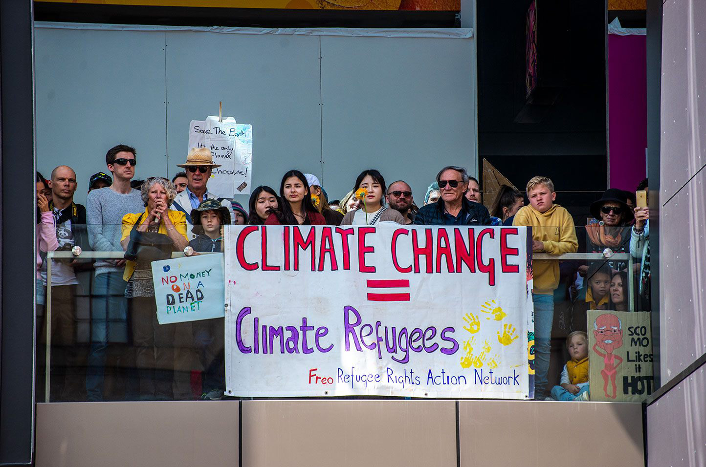 A crowd gathers and looks over a balustrade. A large banner is hung over the balustrade which reads 'Climate Change=Climate Refugees. Freo Refugee Rights Action Network'. Other placards are also held around it, including one that reads 'No money on a dead planet' and 'Sco Mo likes it hot' with a caricature of the Prime Minister in a bikini.