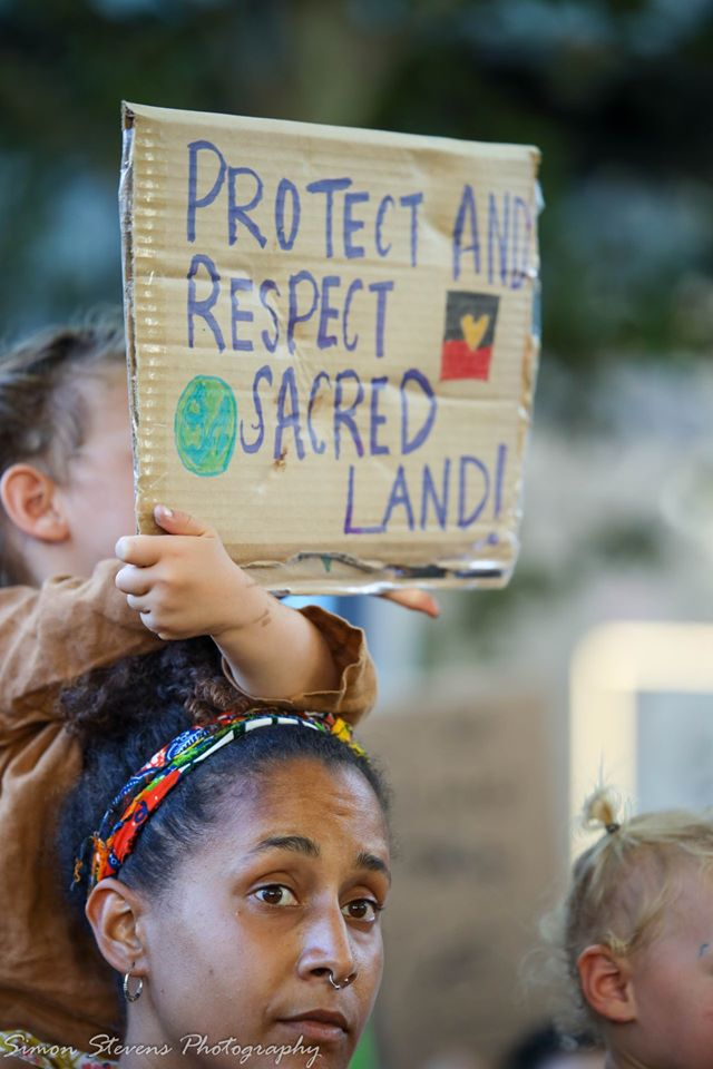A small child sits on a woman's shoulders. The child holds a cardboard placard in front of their face which reads 'Protect and Respect Sacred Land!'. The sign also features a drawing of planet earth and the Aboriginal flag with a yellow heart at its centre.