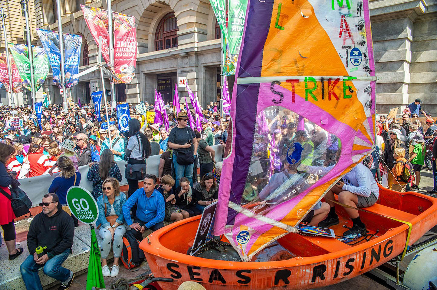 A large crowd fills a city square. A bright orange and pink painted boat sits in the centre with 'Strike' written on the sail and 'Seas R Rising' written on the side of the boat. Surrounding protesters hold various banners and placards.