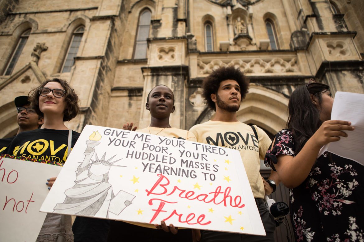 A group of young people stand in front of a church building. The central placard shows a depiction of the statue of liberty and reads 'Give me your tired, your poor, your huddled masses yearning to Breathe Free'.