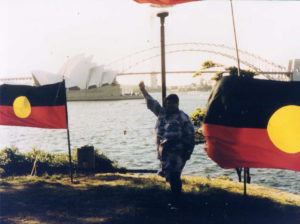 Ruby Langford Ginibi stands near the river, fist raised in the air and flanked by Aboriginal flags. The Sydney Opera House and Harbour Bridge is in the background.