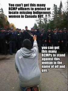 A row of intimidating RCMP (Royal Canadian Mounted Police) officers stand looking at an Indigenous woman who kneels on the road, raising a feather up into the air in defiance. She has her back to the camera. Text overlayed on the photo reads 'You can't get this many RCMP officers to protect or locate missing Indigenous women in Canada BUT....you can get this many RCMP officers to stand against this woman in the name of oil and gas'.