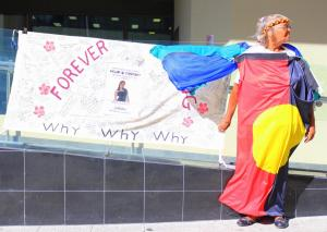 Nana Carol Roe draped in an Aboriginal flag stands outside Perth Coroner's Court, Whadjuk Country (Perth), 14 March 2016