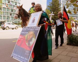 Aunty Carol Roe marching at National Day of Emergency: 25 Years since the RCIADIC, a police officer on a horse follows her, Whadjuk Country (Perth), 15 April 2016