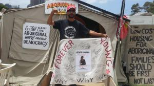 Shaun Harris raises his fist and holds banner for Ms Dhu at the Aboriginal Tent Embassy, Canberra, 2014.