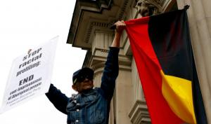 A man holds up an Aboriginal flag in resistance and placard that says 'Stop Racial Profiling' at protest to mark tne Year Anniversary of Ms Dhu's death in custody, Narrm (Melbourne), 4 August 2015