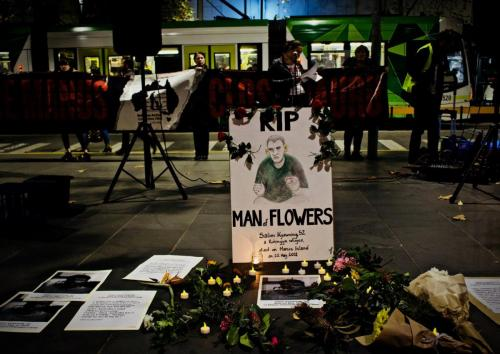 Flowers laid in front of hand drawn portrait of Salim at Vigil for Salim, Narrm, Kulin Nations (Melbourne), 2018.