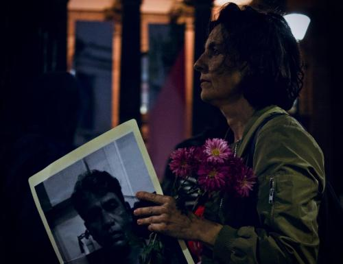 A woman holds a photo of Salim and flowers at Vigil for Salim, Narrm, Kulin Nations (Melbourne), 2018.