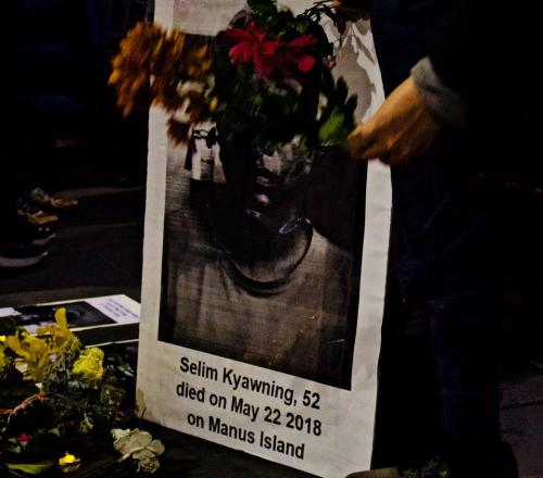 Flowers held in front of poster featuring Salim's photo at Vigil for Salim, Narrm, Kulin Nations (Melbourne), 2018.