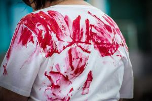 Bloody handprints on back of demonstrator representing someone who had died on Manus or Nauru at 'Evacuate Now, Remember Reza Barati (4 years)', Whadjuk Country (Perth), 17 February 2018.