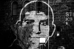 Projection of digital portrait of Reza Barati on stone wall at one year anniversary action, Perth, 2015.