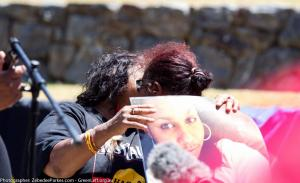 Two women holding a photo of Ms Dhu embrace at G20 Protest, Brisbane, 14 November 2014