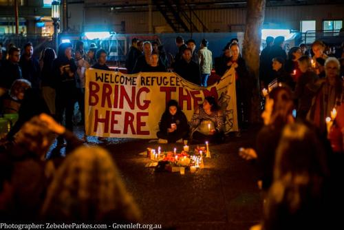 Crowd gathers with candles and 'Bring Them Here' banner at Vigil for Salim, Sydney, 2018. Photo: Zebedee Parkes.