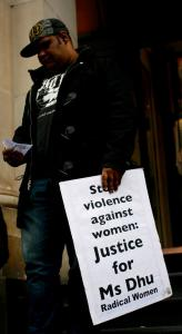 A man holds a placard that says 'Stop violence against women: Justice for Ms Dhu', Narrm (Melbourne), 4 August 2015
